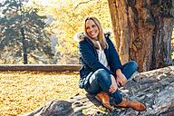 Happy woman enjoying autumn in a forest sitting on a trunk - CHAF001582