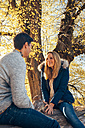 Happy couple enjoying autumn in a forest sitting on trunk - CHAF001585