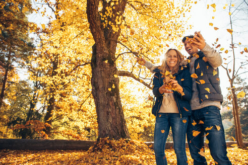 Happy couple having fun in autumn in a forest - CHAF001588