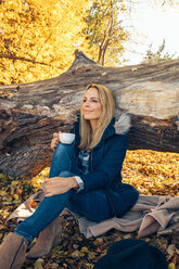 Smiling woman holding cup in autumn forest - CHAF001594