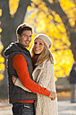 Happy couple embracing in autumn forest - CHAF001597