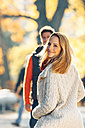 Happy couple enjoying autumn in a park - CHAF001600