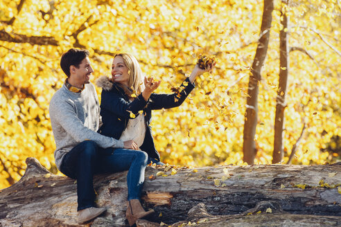 Happy couple having fun in autumn in a forest sitting on a trunk - CHAF001612