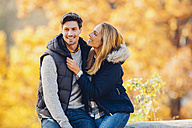 Happy couple enjoying autumn in a forest sitting on a trunk - CHAF001615