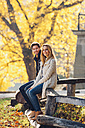 Happy couple sitting on wooden railing in autumnal park - CHAF001633