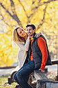 Happy couple enjoying autumn in a park - CHAF001636