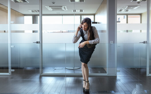 Businesswoman telephoning with smartphone at corridor of an office - MGOF001345