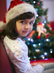 Portrait of smiling little girl wearing Christmas hat - MGOF001365