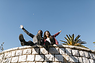 Spain, Tarragona, exuberant young couple sitting on stone wall - JRFF000399