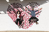 Happy young couple jumping in front of a brick wall with a heart - JRFF000405