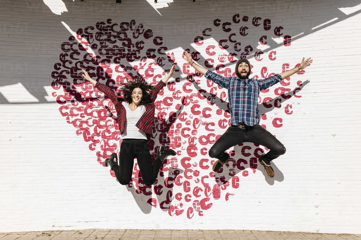 Happy young couple jumping in front of a brick wall with a heart - JRFF000405 - Josep Rovirosa/Westend61