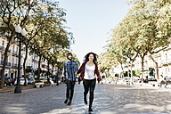Spain, Tarragona, happy young couple running in the city - JRFF000414