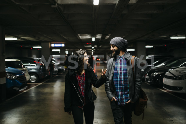Smiling young couple talking in a parking garage - JRFF000420
