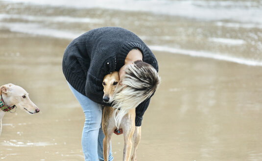Spain, Llanes, young woman kissing her greyhound on the beach - MGOF001369