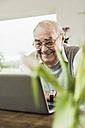 Portrait of happy senior man using laptop at home - UUF006569