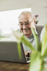 Portrait of happy senior man using laptop at home - UUF006569