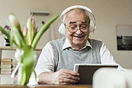 Senior man using mini tablet and headphones for skyping at home - UUF006572