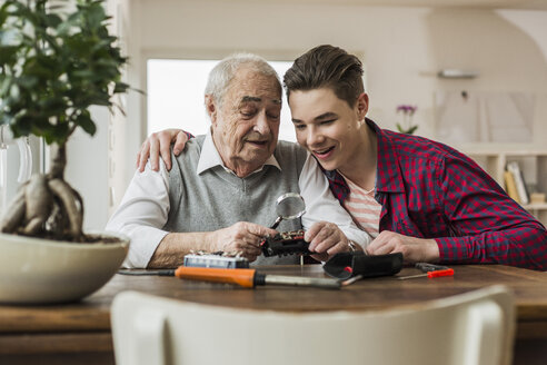 Portrait of senior man and grandson with toy train at home - UUF006581
