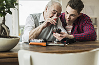 Senior man repairing toy train together with his grandson - UUF006584