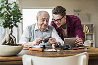 Portrait of senior man and grandson with toy train and mini tablet at home - UUF006587
