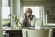 Portrait of sad senior man looking through window - UUF006590