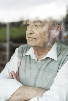 Portrait of pensive senior man with crossed arms looking through window - UUF006593