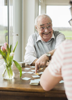 Portrait of laughing senior man playing memory with his grandson - UUF006596