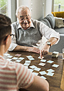Senior man playing memory with his grandson - UUF006599