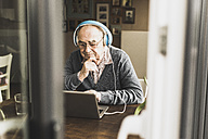 Senior man using laptop and headphones at home - UUF006611