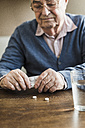 Senior man taking tablets out of blister pack, close-up - UUF006614