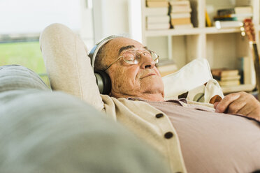 Senior man lying on the couch hearing music with headphones - UUF006629