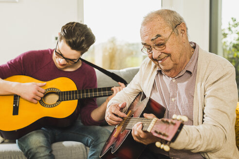 Portrait of senior man playing guitar with his grandson - UUF006632