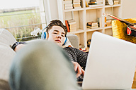 Young man lying on couch using laptop and headphones - UUF006638
