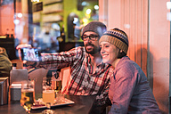 Couple in a winter terrace bar behind a glass taking a selfie - JASF000379