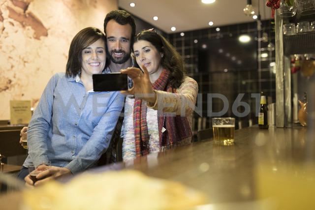 Three friends taking selfie in a bar - JASF000382