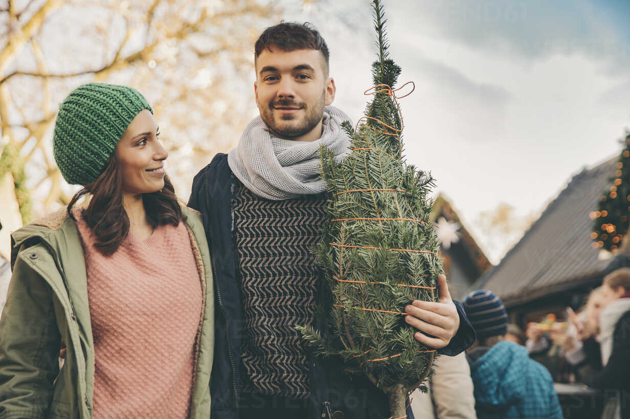 Happy couple with a tree on the Christmas Market - MFF002644 - Mareen Fischinger/Westend61