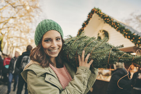 Happy woman with a wrapped-up tree walking over the Christmas Market - MFF002650