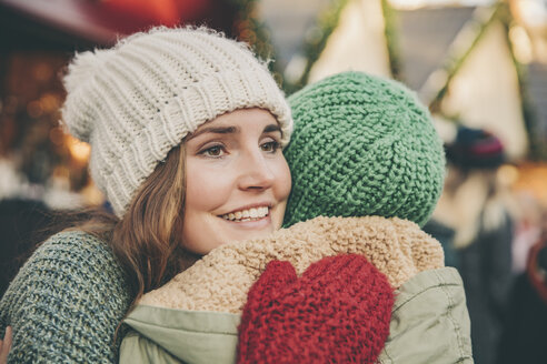 Happy woman hugging a friend on the Christmas Market - MFF002659