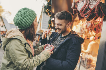 Woman receiving a gingerbread heart from her boyfriend on the Christmas Market - MFF002668