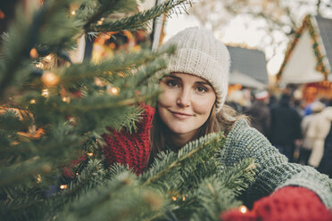 Woman looking trough conifer branches on the Christmas Market - MFF002671