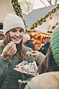 Two women having a hot waffle on the Christmas Market - MFF002680