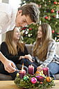 Teenage boy lighting candle on Advent wreath - LBF001372