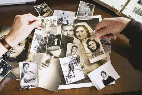 Hands of senior couple holding old photographies of themselves - GEMF000719