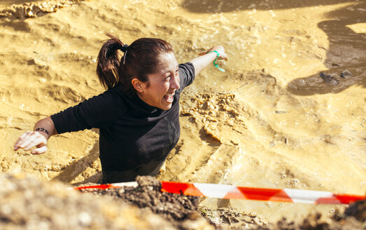 Participants in extreme obstacle race, running through mud - MGOF001377