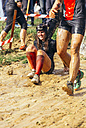 Participants in extreme obstacle race sliding in mud - MGO001380