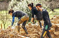 Participants in extreme obstacle race, running through mud - MGOF001383