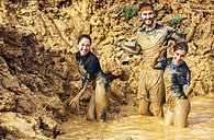 Participants in extreme obstacle race, running through mud - MGOF001386