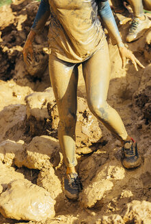 Participants in extreme obstacle race, running through mud - MGOF001389