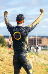Participant in extreme obstacle race cheering, rear view - MGOF001392