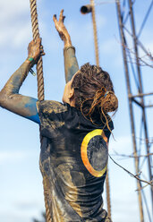 Participant in extreme obstacle race climbing up a rope - MGOF001398